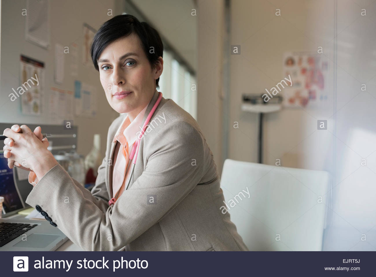 Portrait of serious doctor with hands clasped - Stock Image