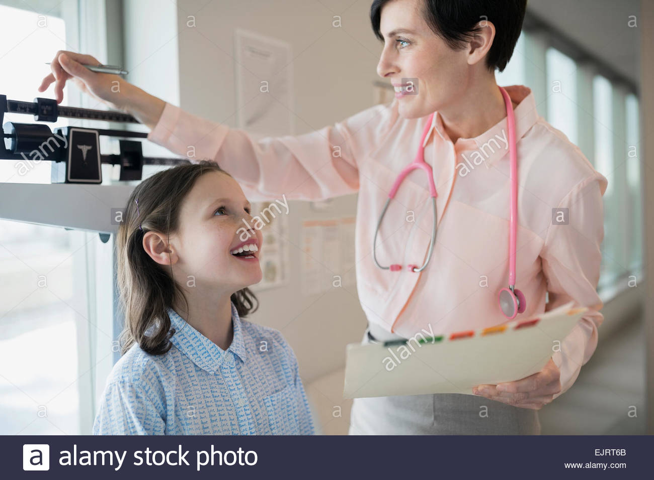 Pediatrician measuring girls weight on scale in clinic - Stock Image