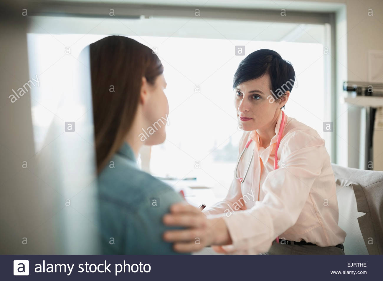 Caring doctor consoling patient in clinic office - Stock Image
