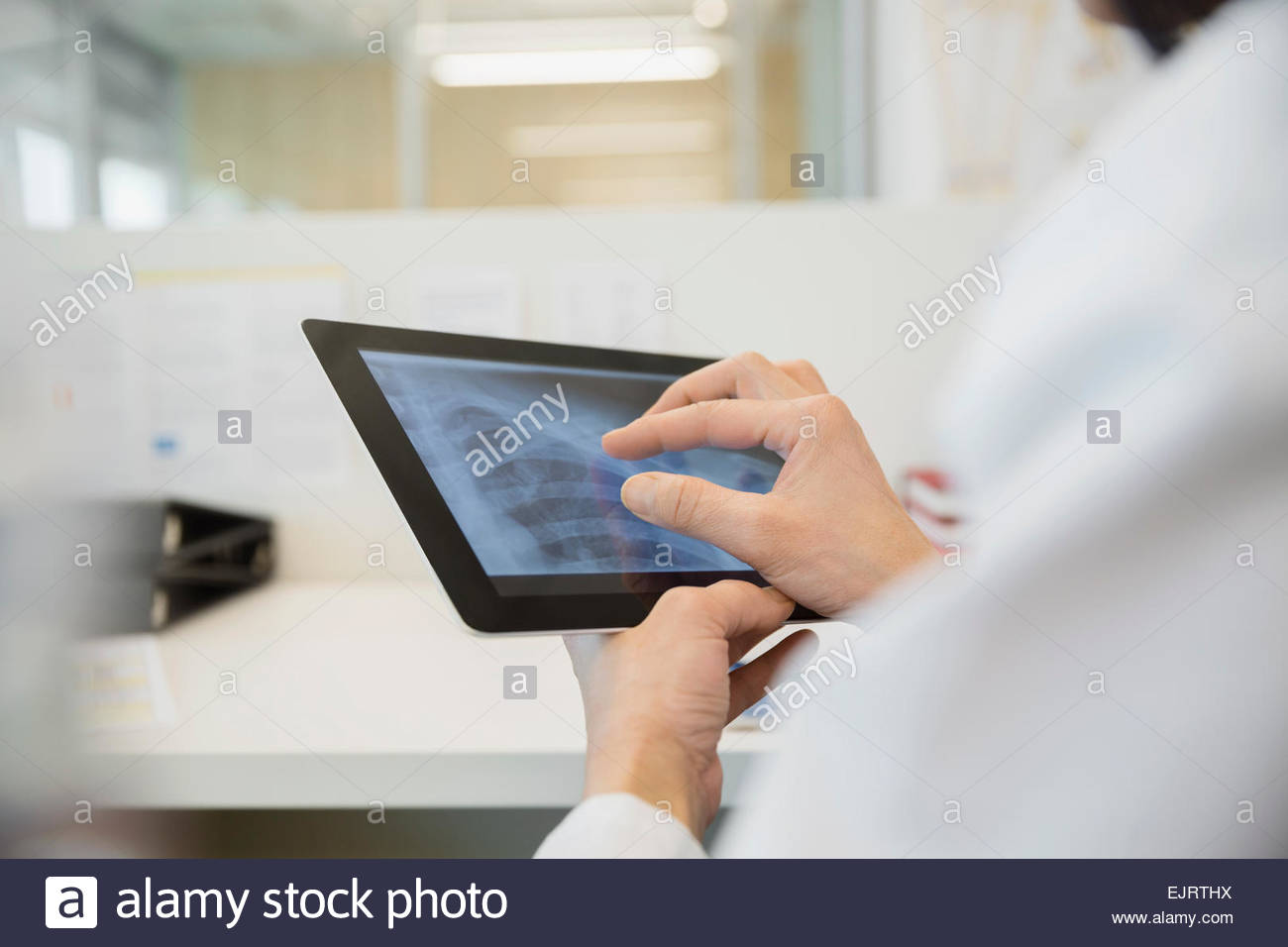 Doctor examining x-ray on digital tablet - Stock Image