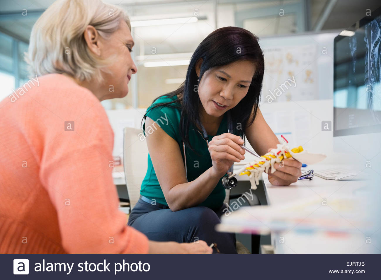 Doctor showing patient spine model in clinic - Stock Image