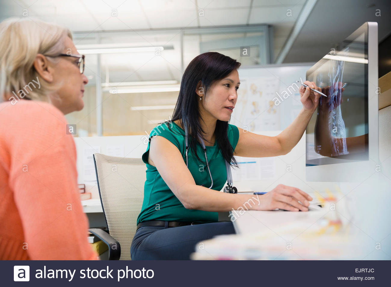 Doctor reviewing x-rays on computer with patient - Stock Image