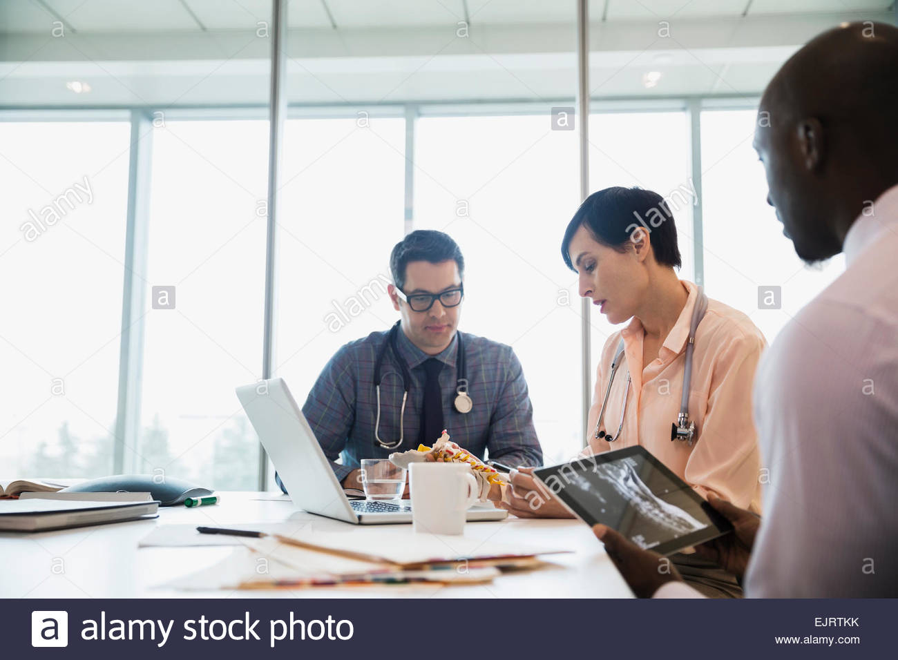 Doctors discussing bone model and viewing x-rays - Stock Image