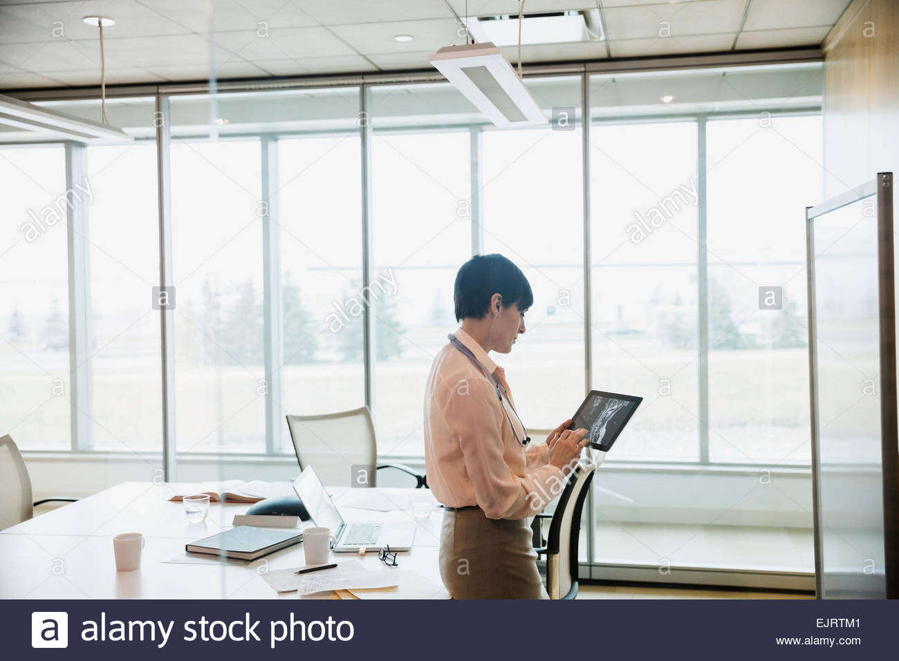 Doctor examining x-rays on digital tablet - Stock Image