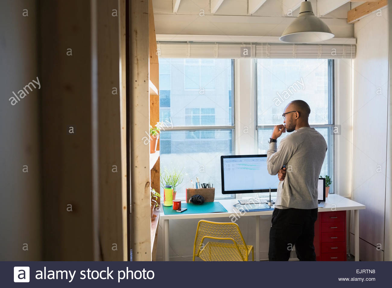 Designer looking out office window - Stock Image