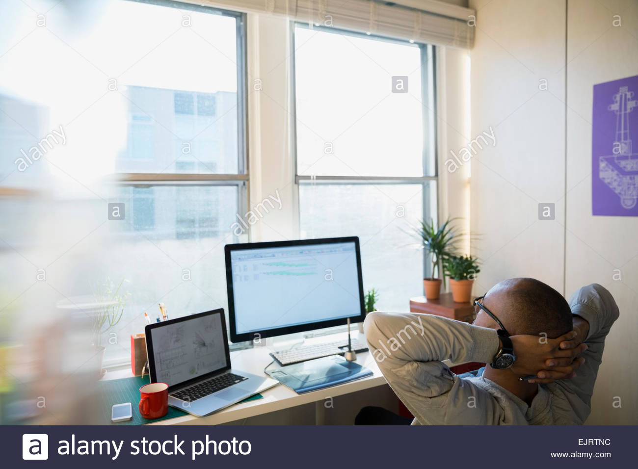 Designer with hands behind head in office - Stock Image
