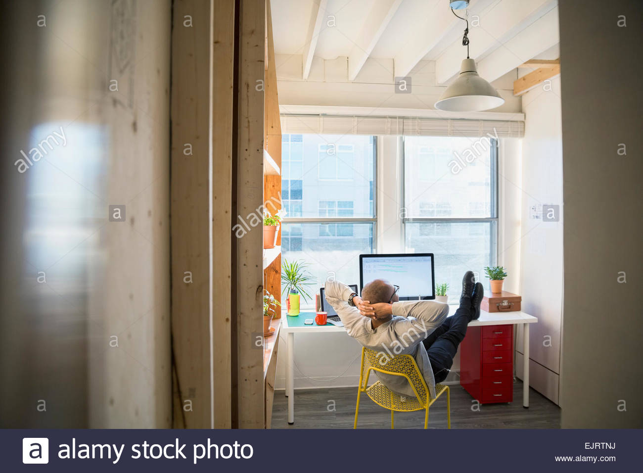 Designer with feet up on office desk - Stock Image