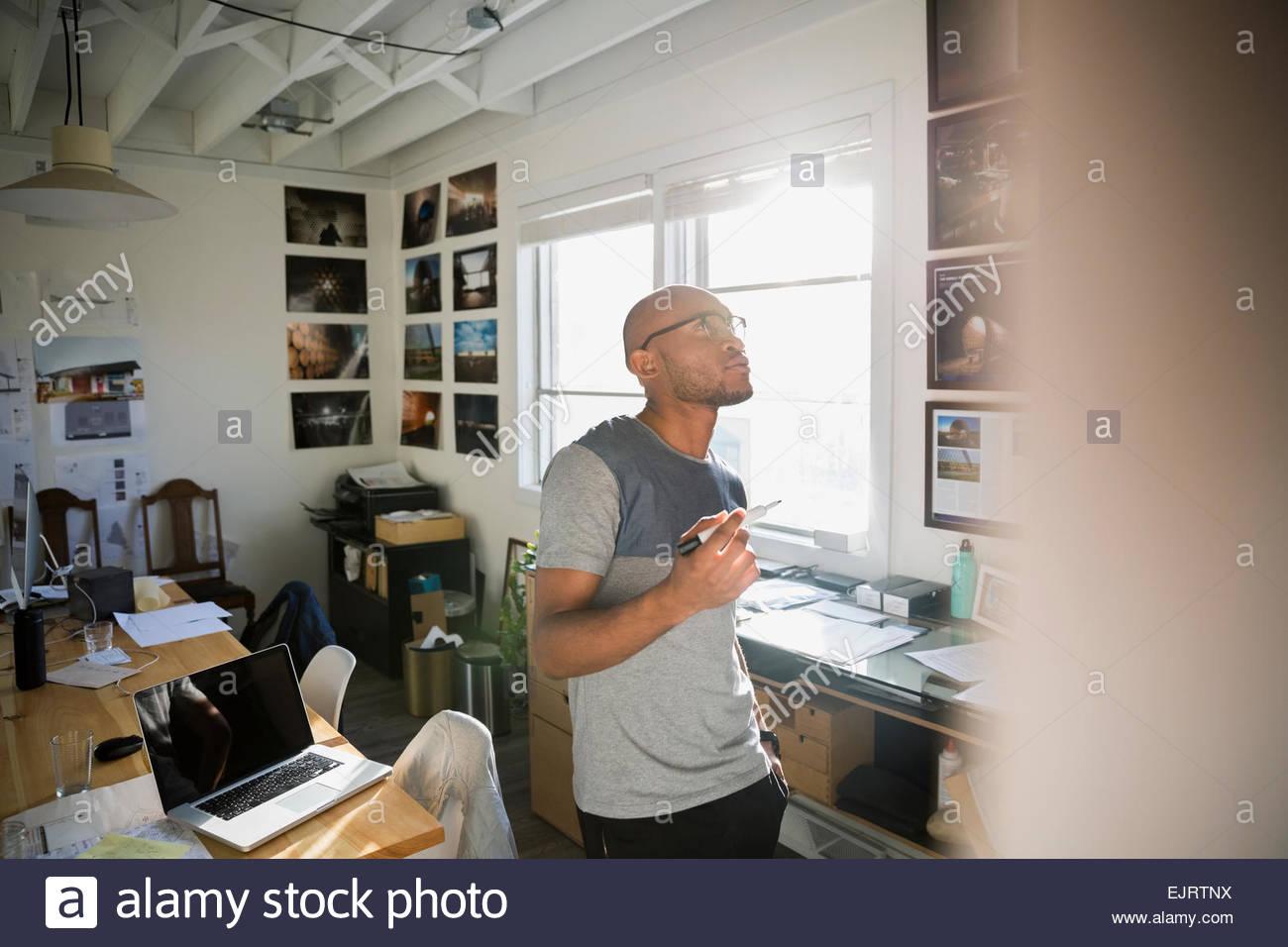 Pensive designer looking up in office - Stock Image