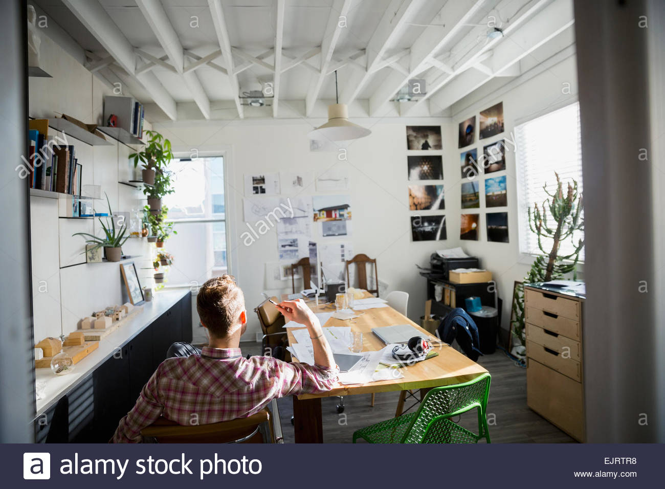 Architect viewing blueprints in office - Stock Image