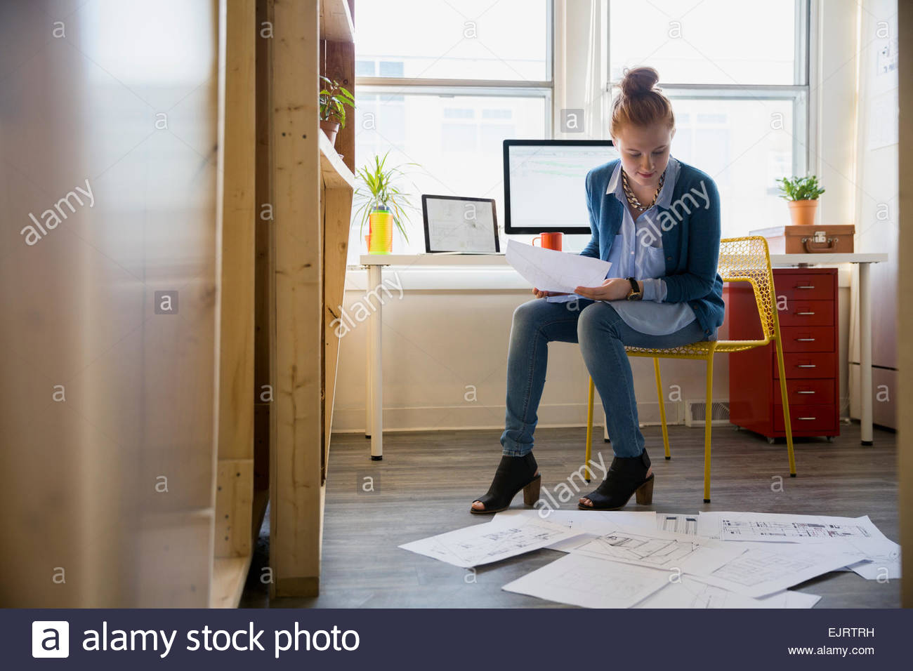 Architect reviewing blueprints on office floor - Stock Image
