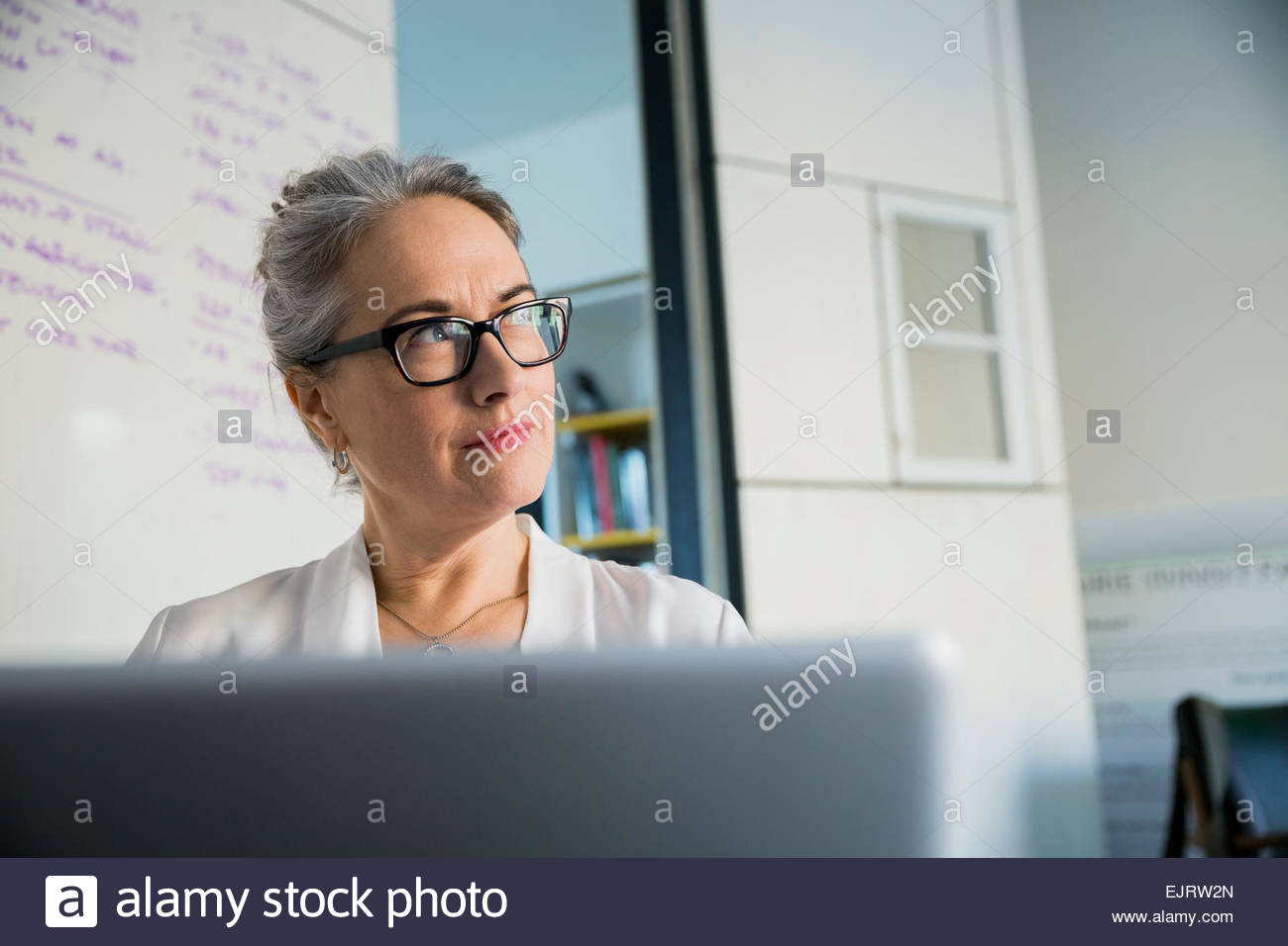 Pensive businesswoman working at laptop - Stock Image