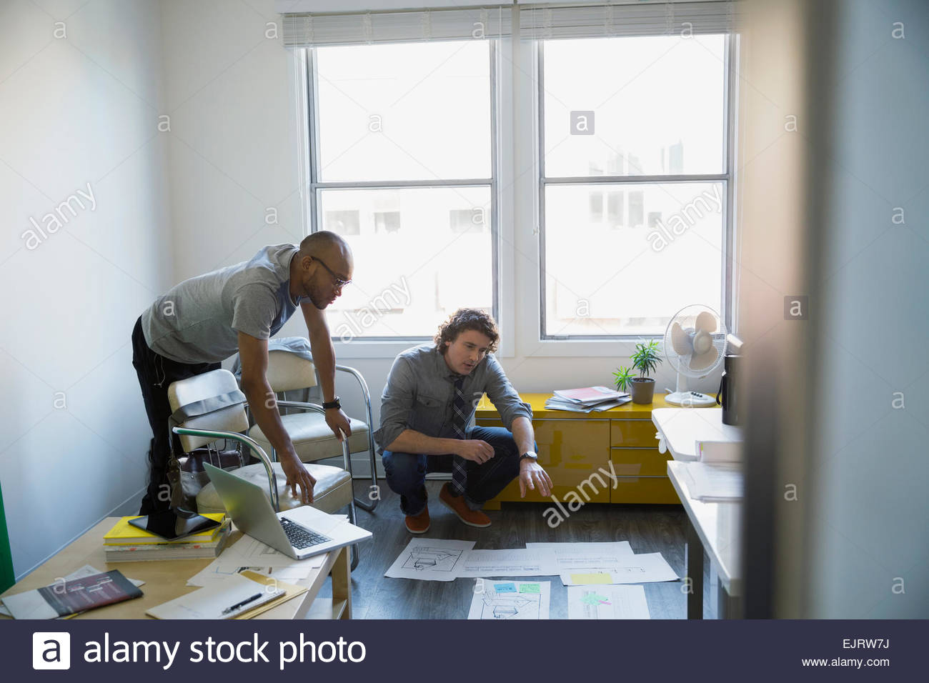 Architects reviewing blueprints on office floor - Stock Image