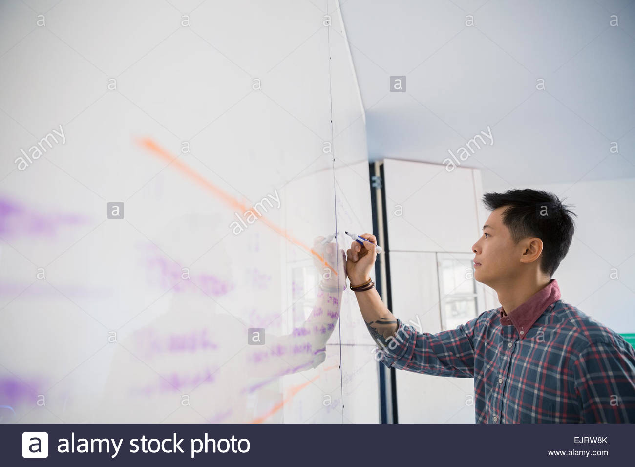 Businessman writing on whiteboard - Stock Image