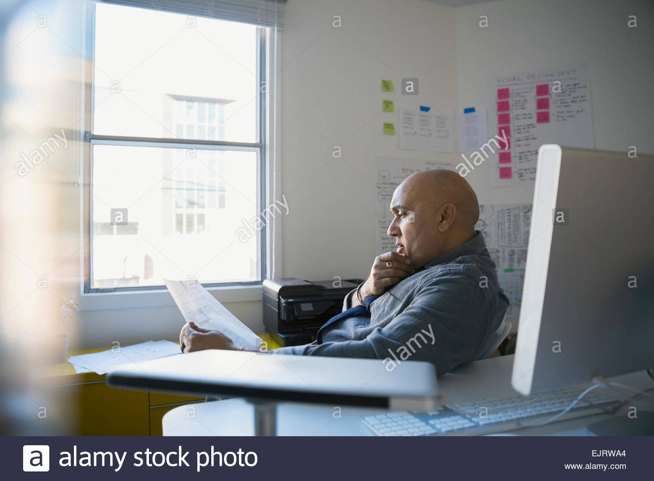 Businessman reading paperwork in office - Stock Image