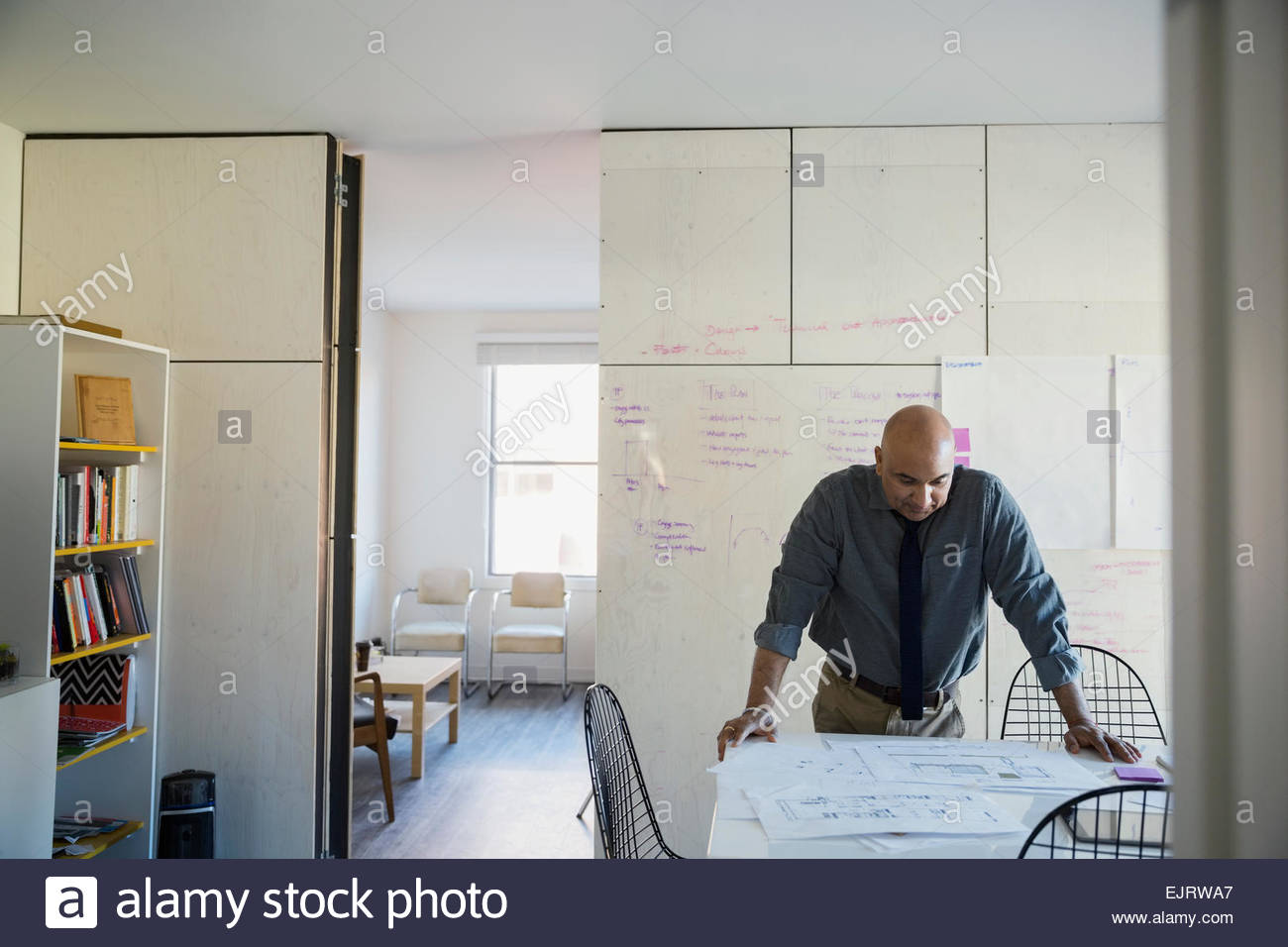 Architect reviewing blueprints in conference room - Stock Image
