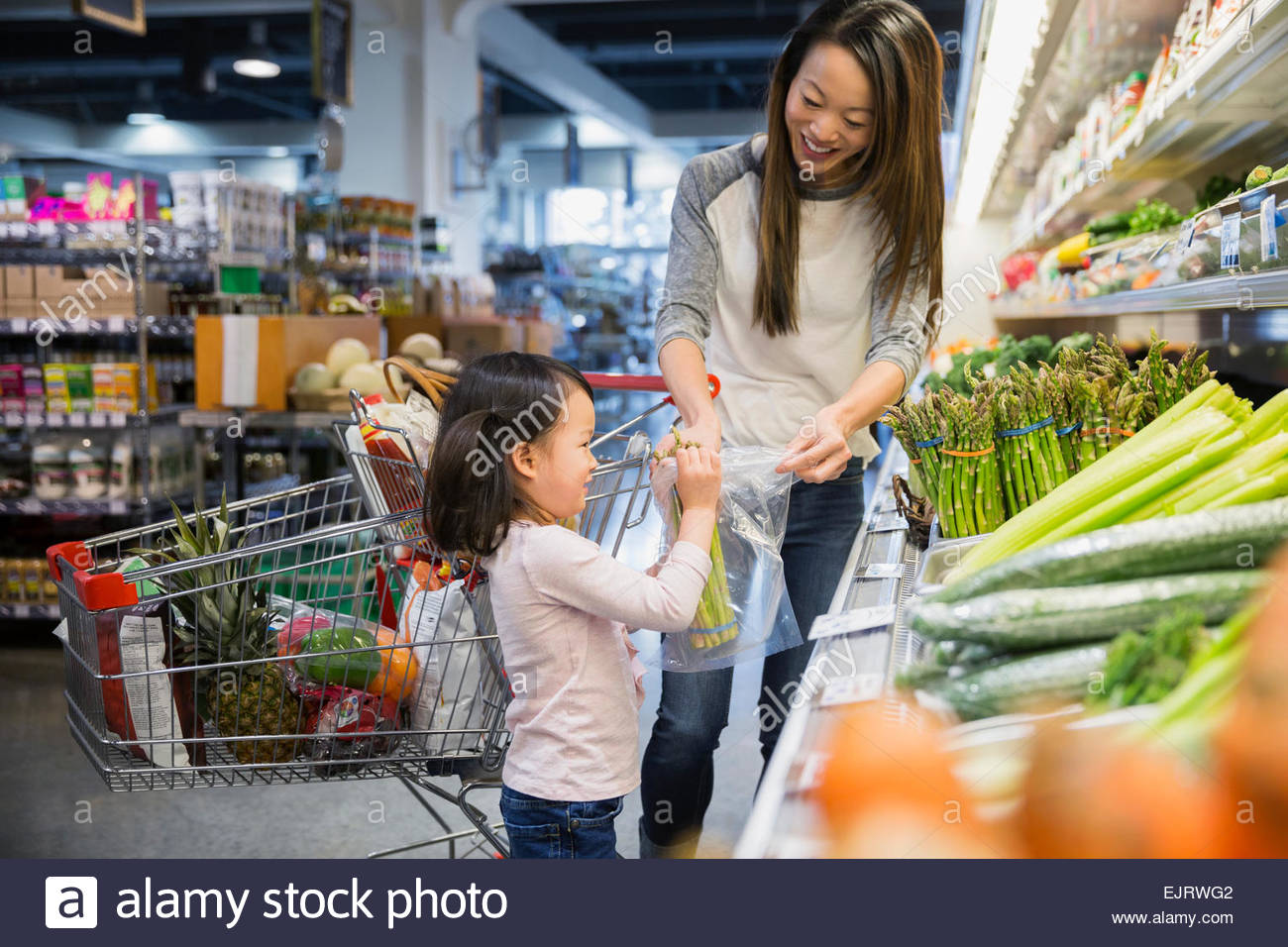 Mother and daughter bagging asparagus in grocery store - Stock Image