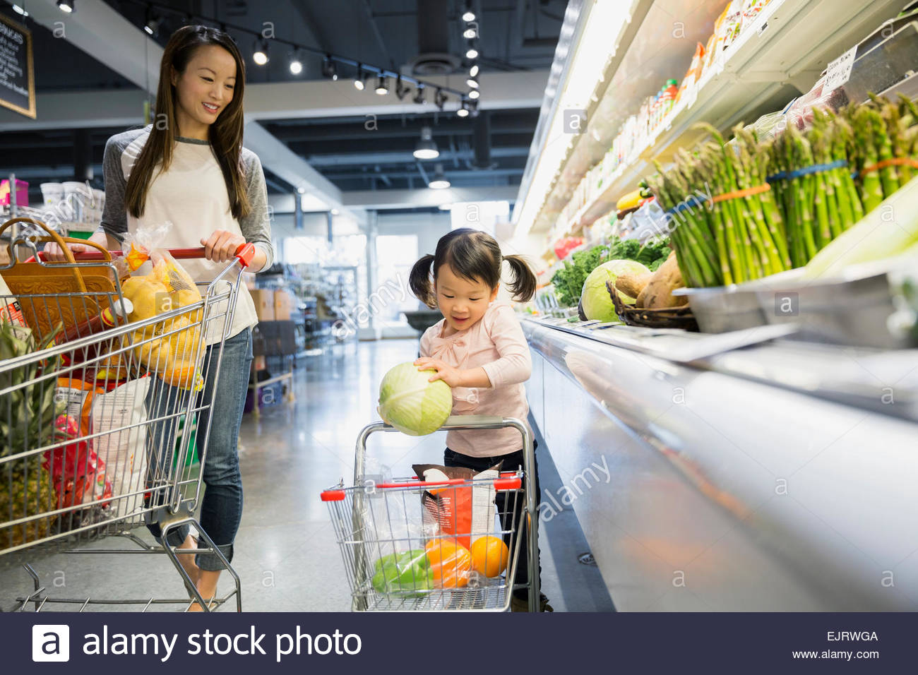 Mother watching daughter place melon in shopping cart - Stock Image