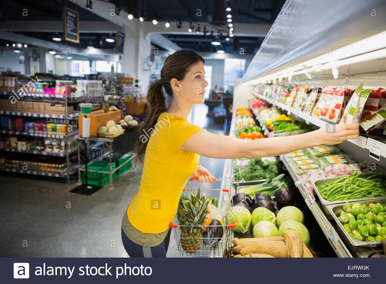 Woman shopping for produce in grocery store - Stock Image