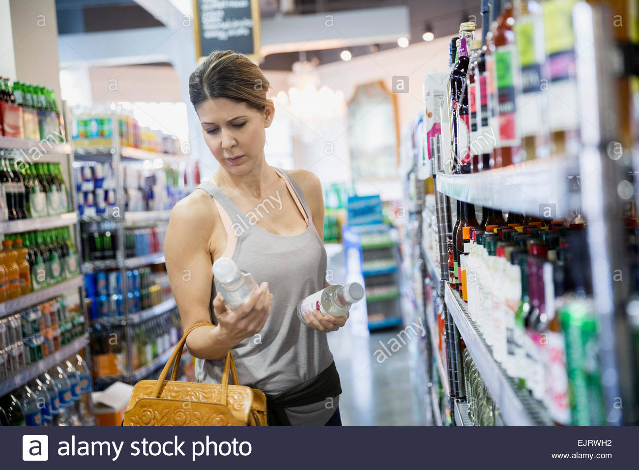 Woman reading labels on bottles in grocery store - Stock Image