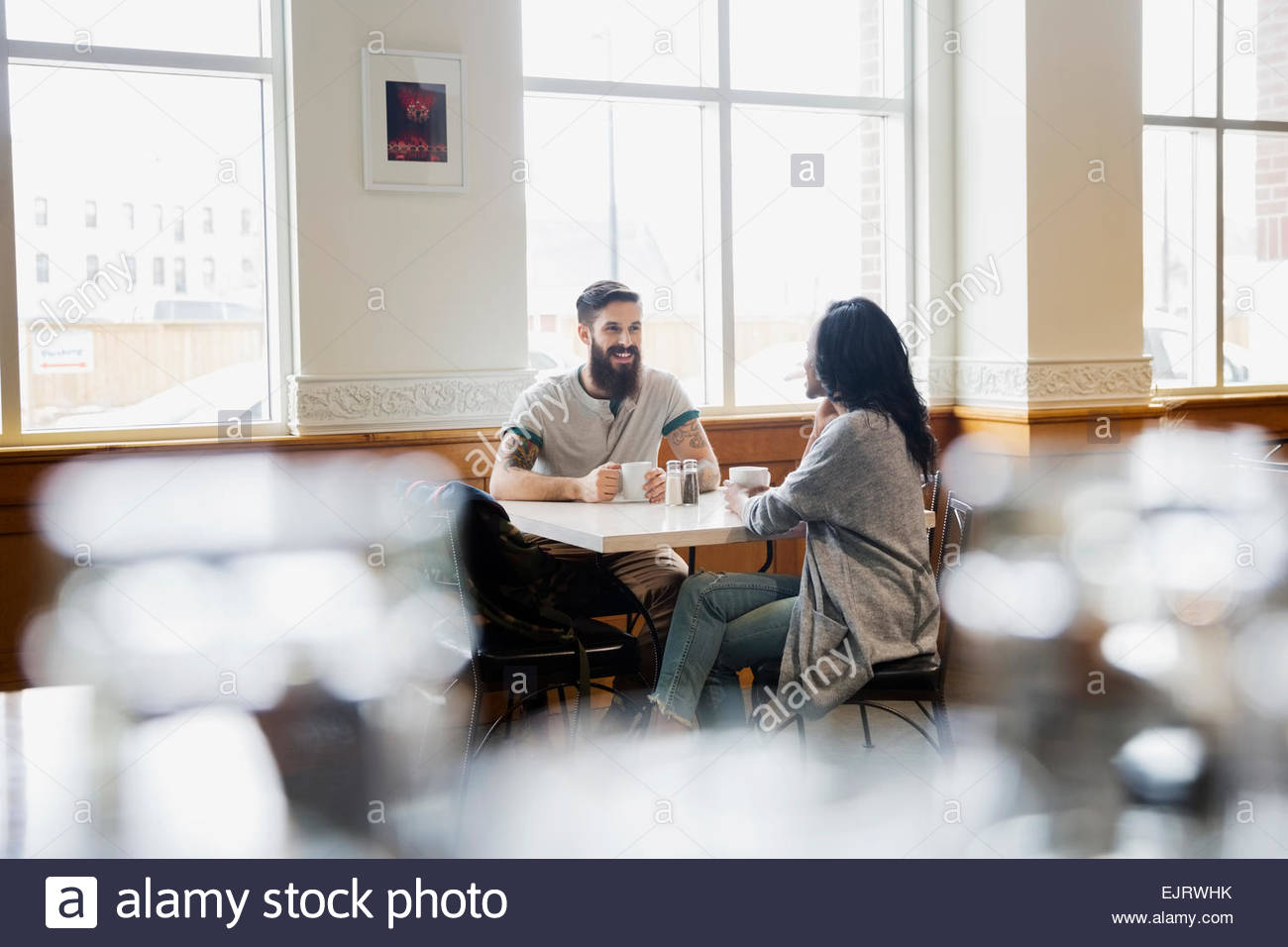 Couple drinking coffee at cafe table - Stock Image