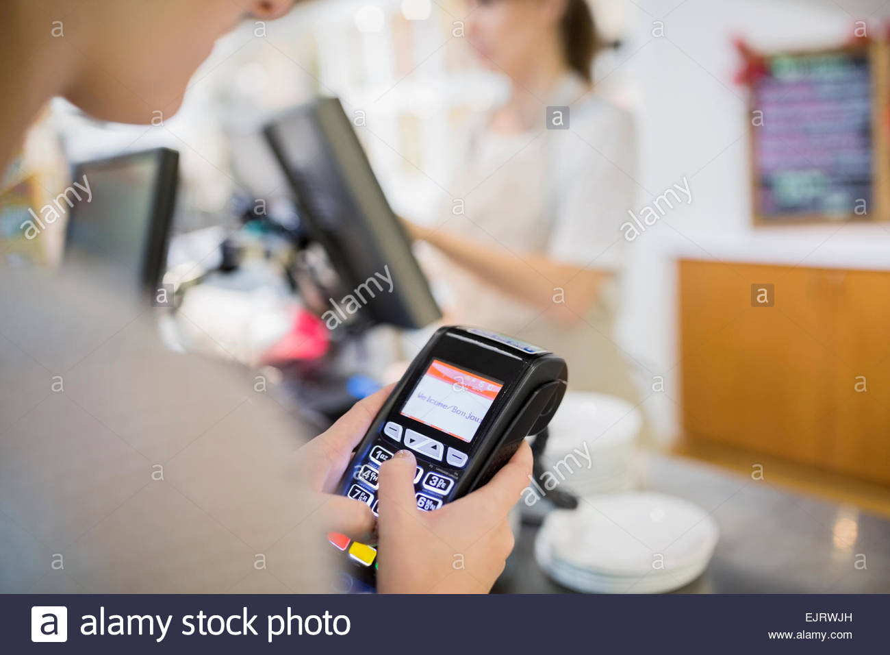 Woman using credit card reader in cafe Stock Photo