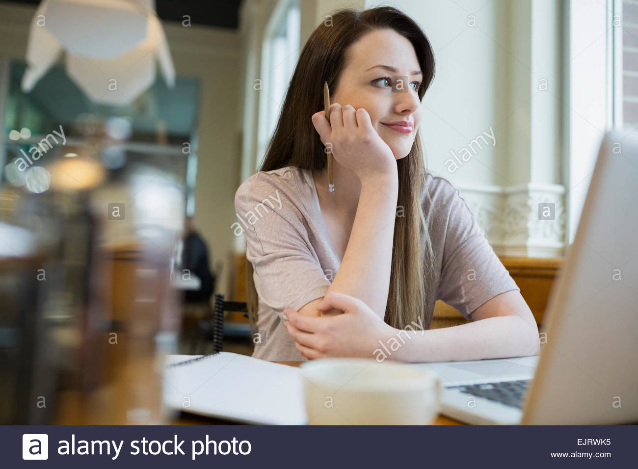Smiling woman looking away at laptop in cafe Stock Photo