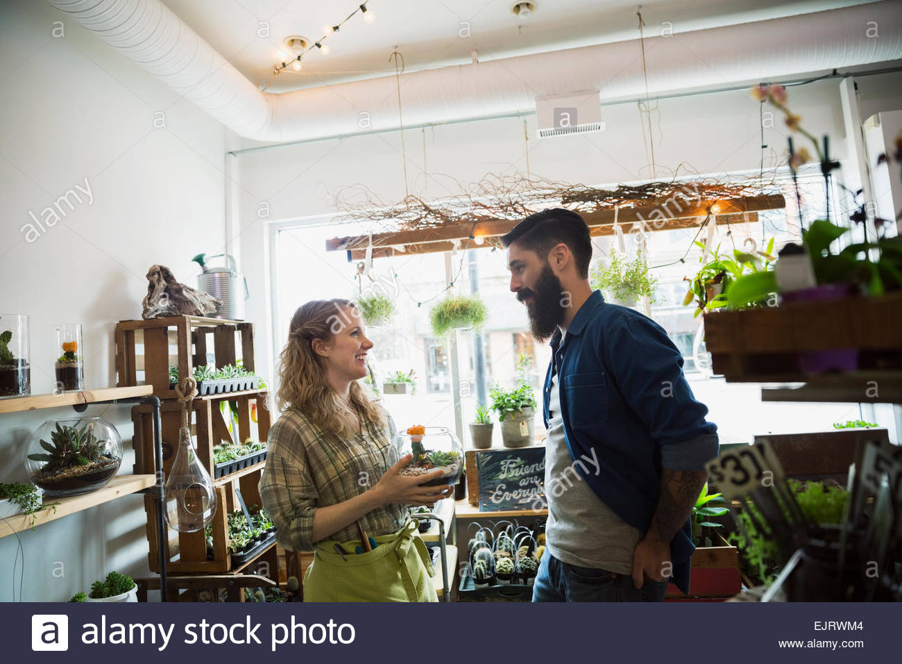 Terrarium Shop Owner Helping Customer With Plants Stock Photo