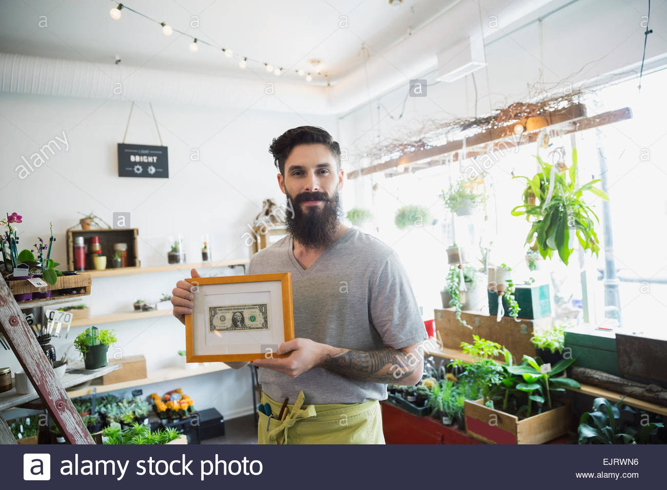Portrait of terrarium shop owner showing first dollar - Stock Image