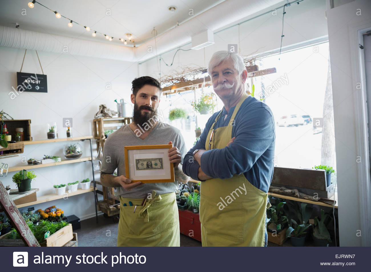 Portrait of terrarium shop owners showing first dollar - Stock Image
