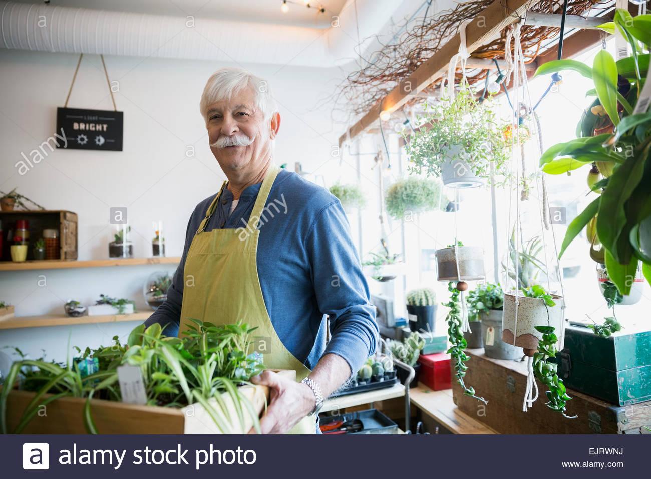 Portrait of confident terrarium shop owner holding plants - Stock Image