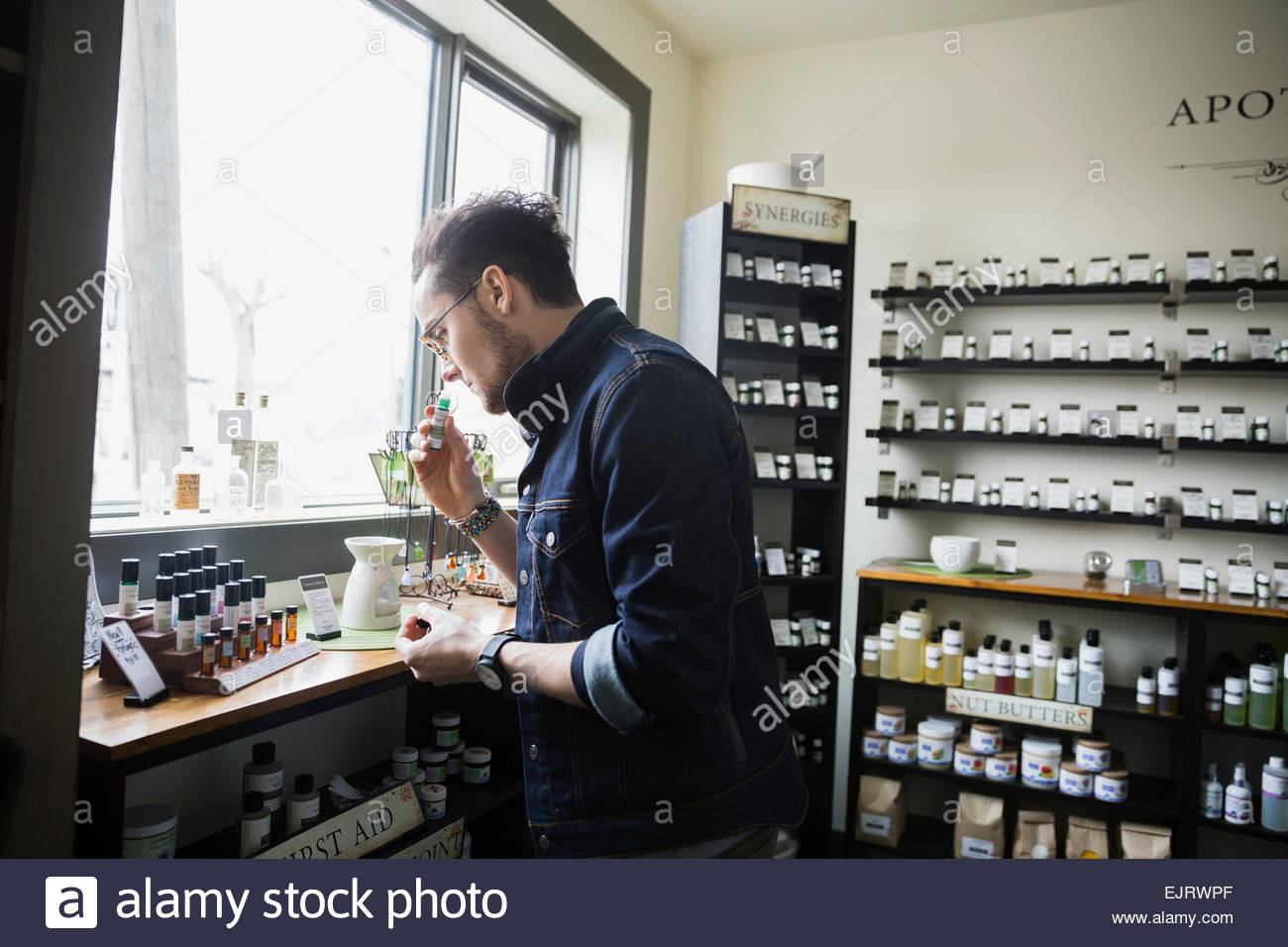 Man smelling essential oils in apothecary shop Stock Photo