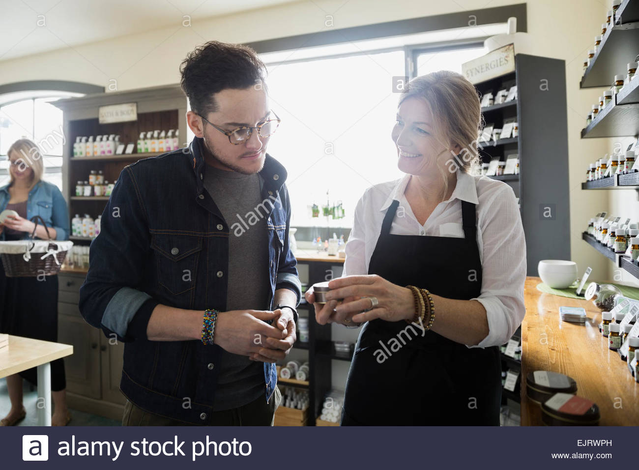 Apothecary shop owner helping man - Stock Image