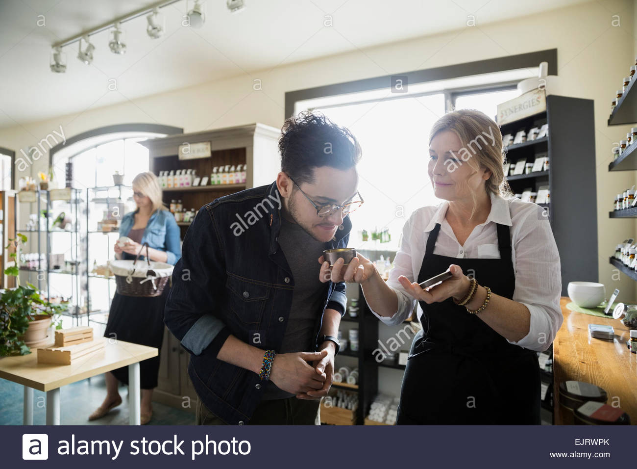 Apothecary shop owner letting man smell candle - Stock Image