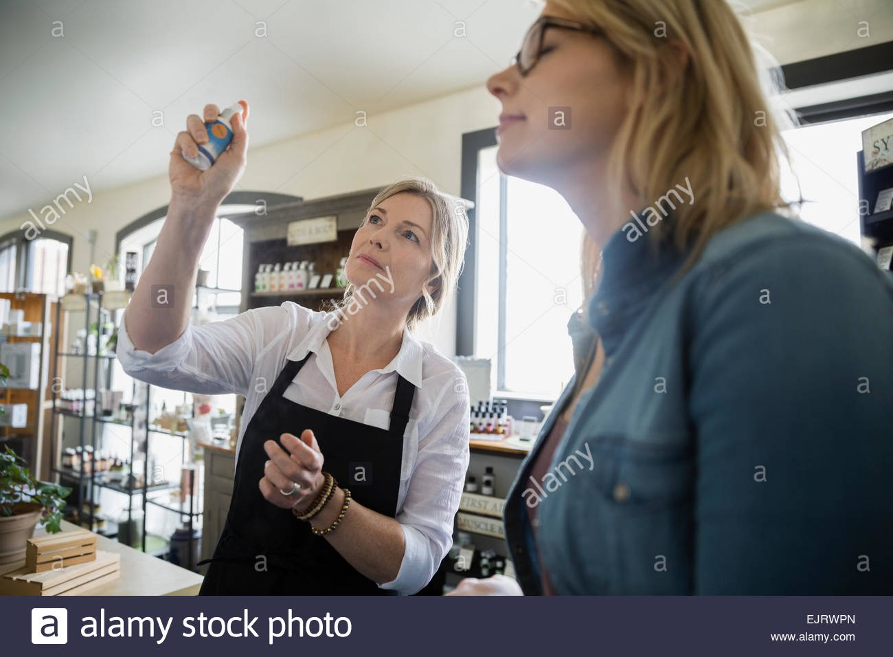 Apothecary shop owner spraying essential oils for woman - Stock Image