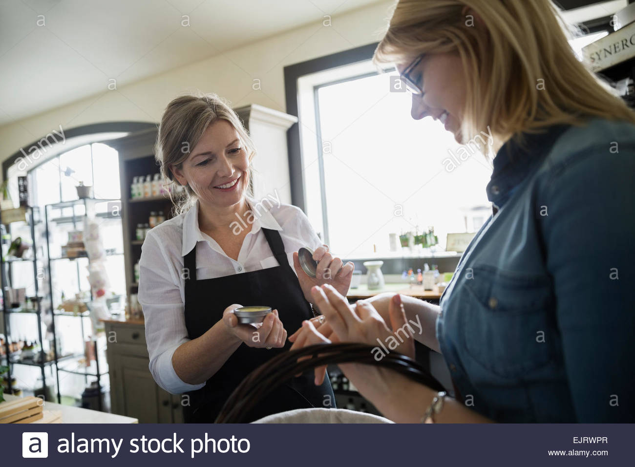 Apothecary shop owner showing woman balm Stock Photo