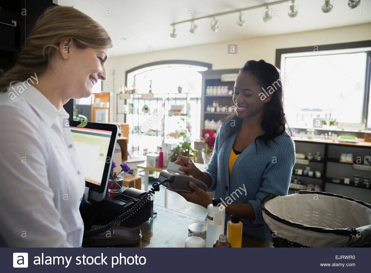 Woman paying with credit card in apothecary shop Stock Photo