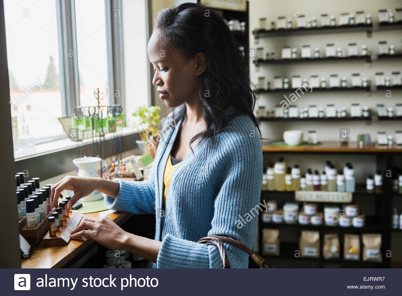 Woman browsing essential oils in apothecary shop - Stock Image