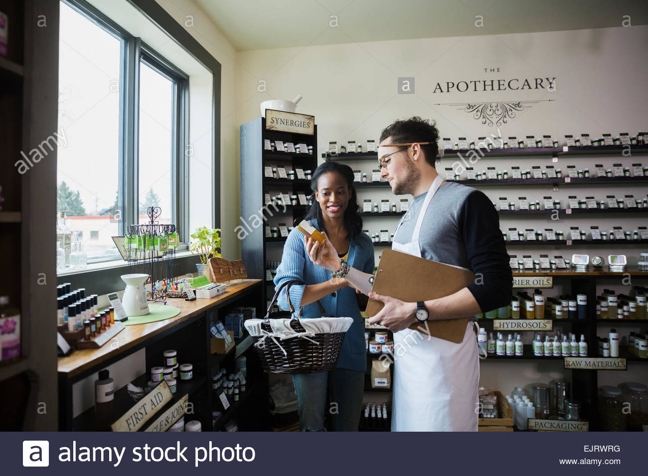 Apothecary shop owner showing customer product Stock Photo