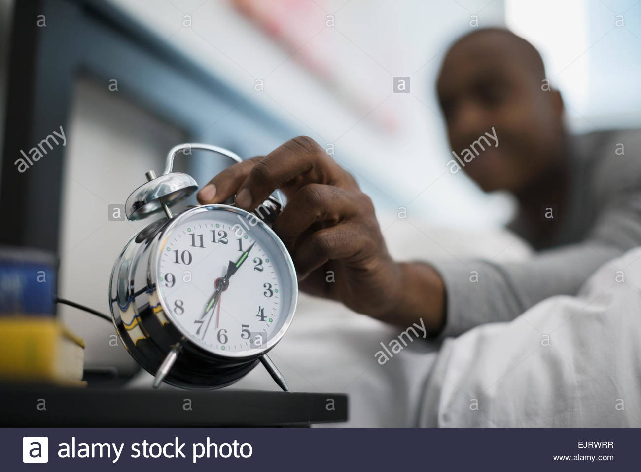 Man awaking to and turning off alarm clock - Stock Image