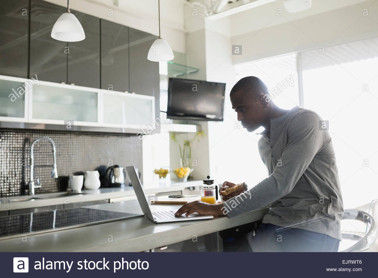 Man Using Laptop At Breakfast Bar In Kitchen Stock Photo ...