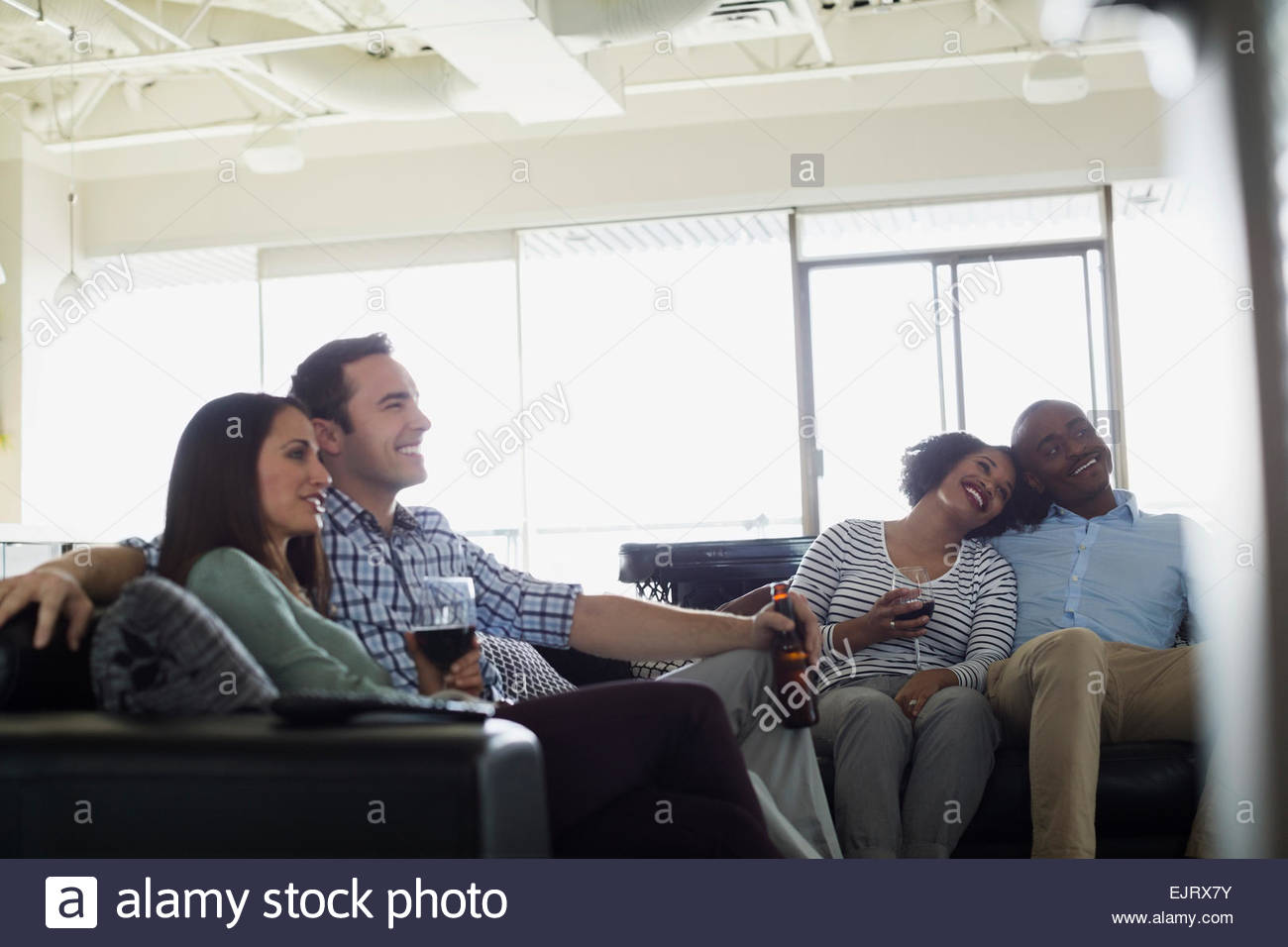 Couples drinking and watching TV on sofas - Stock Image