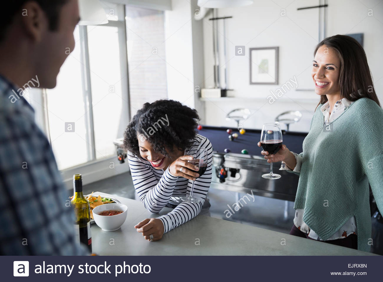 Friends laughing and drinking red wine in kitchen - Stock Image