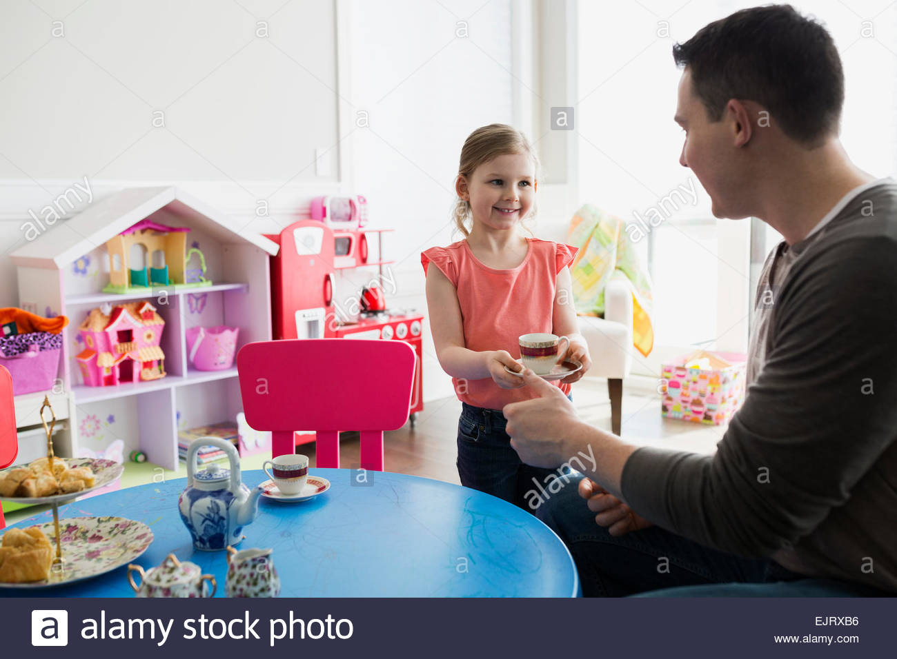 Daughter serving father tea at tea party - Stock Image
