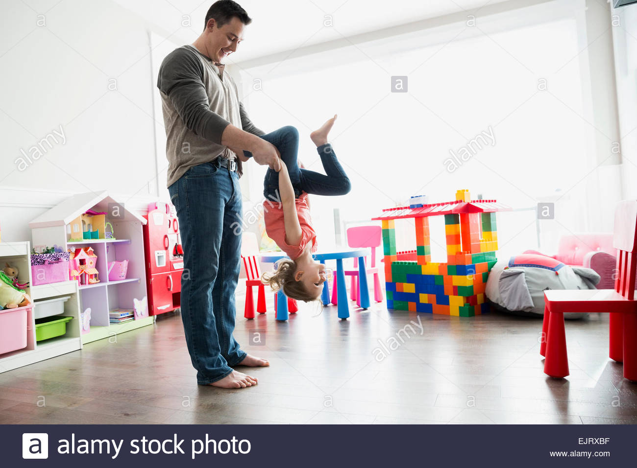 Father flipping daughter upside-down - Stock Image