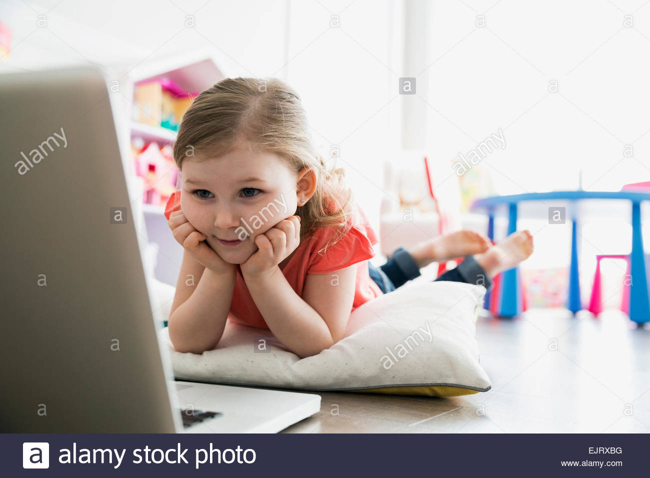 Girl using laptop on floor with pillow - Stock Image