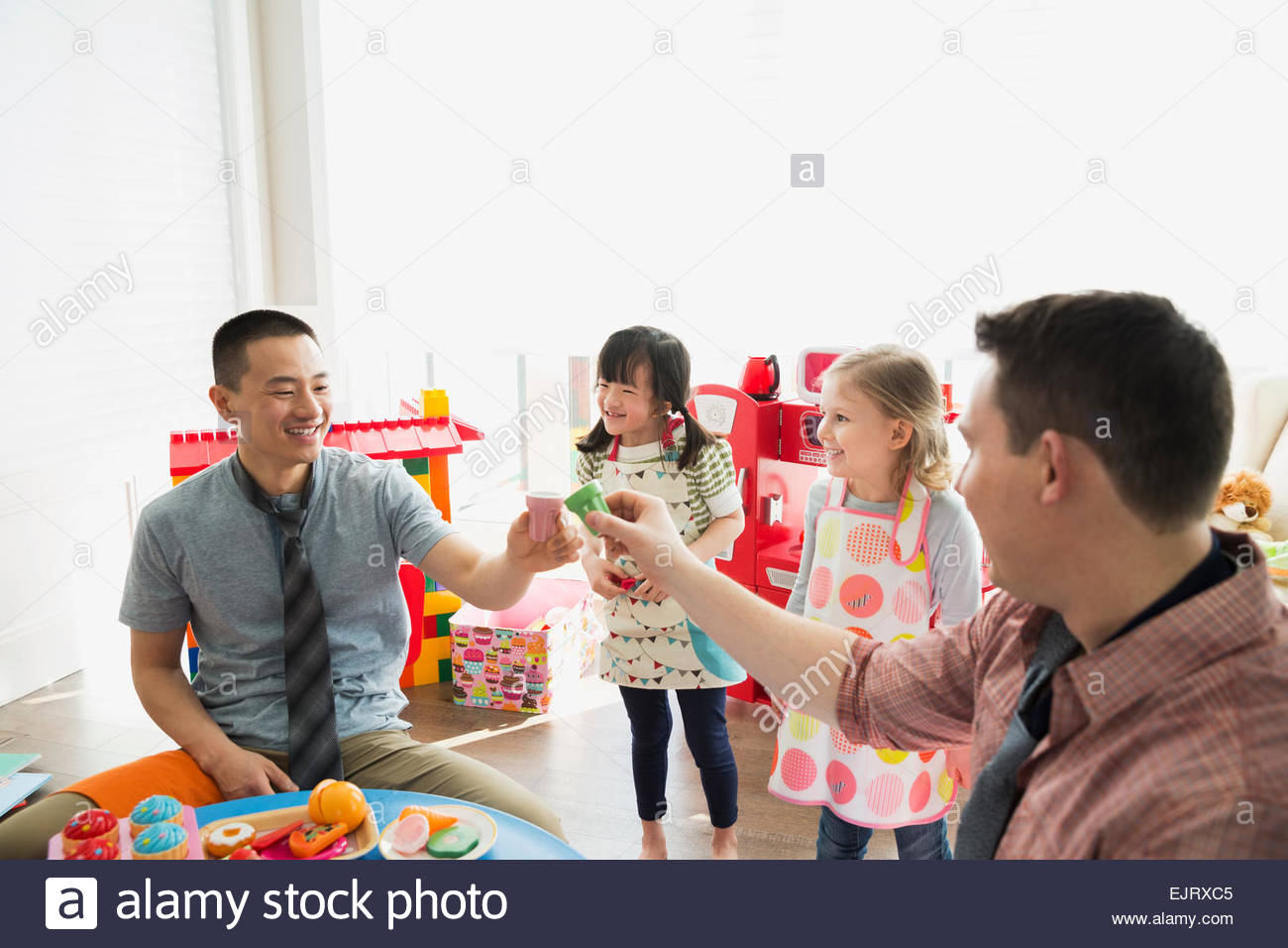 Fathers and daughters playing pretend restaurant - Stock Image