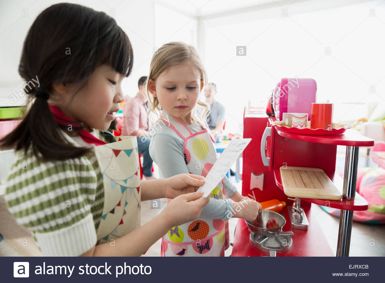 Girls playing pretend restaurant - Stock Image