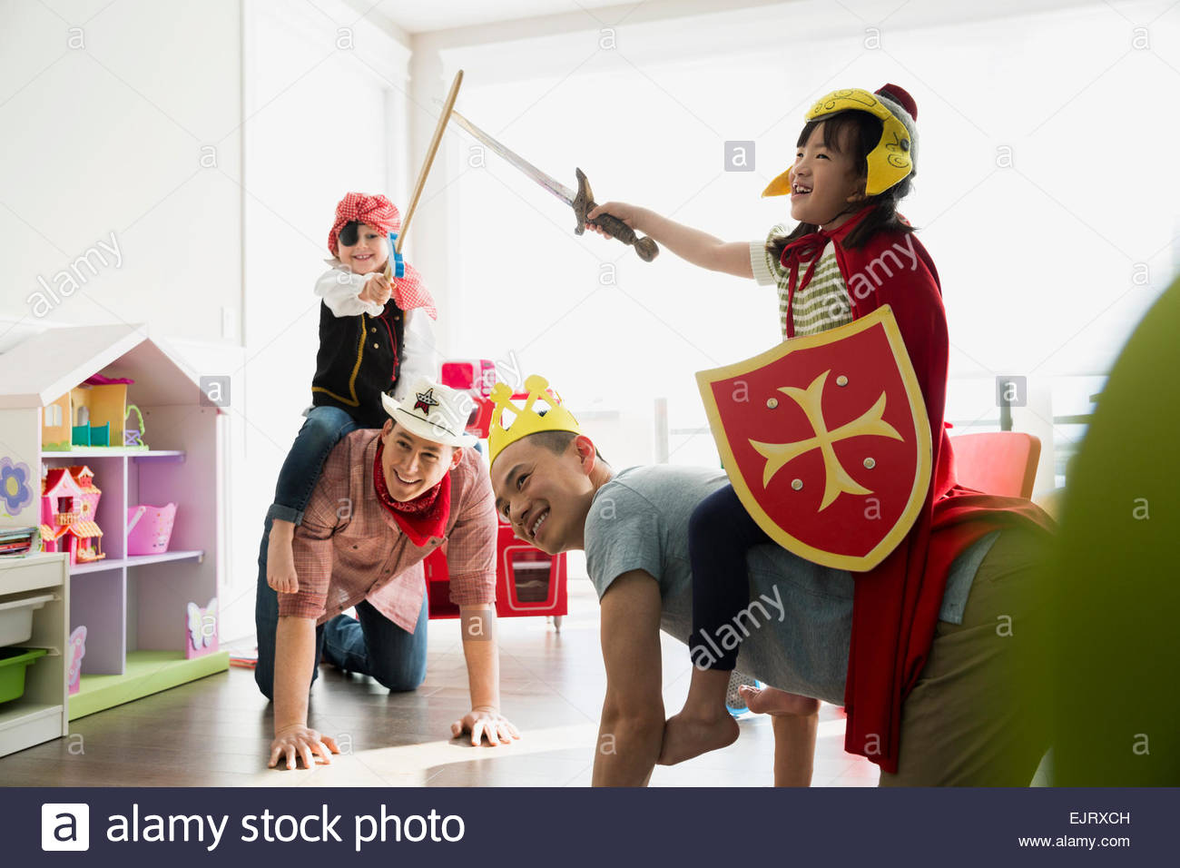 Fathers piggybacking daughters in costumes playing sword fight - Stock Image