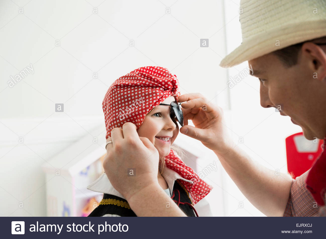 Father adjusting eye patch on daughter pirate costume - Stock Image