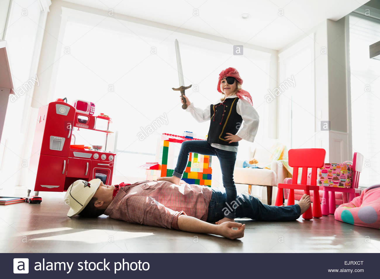 Portrait of daughter in pirate costume conquering father - Stock Image